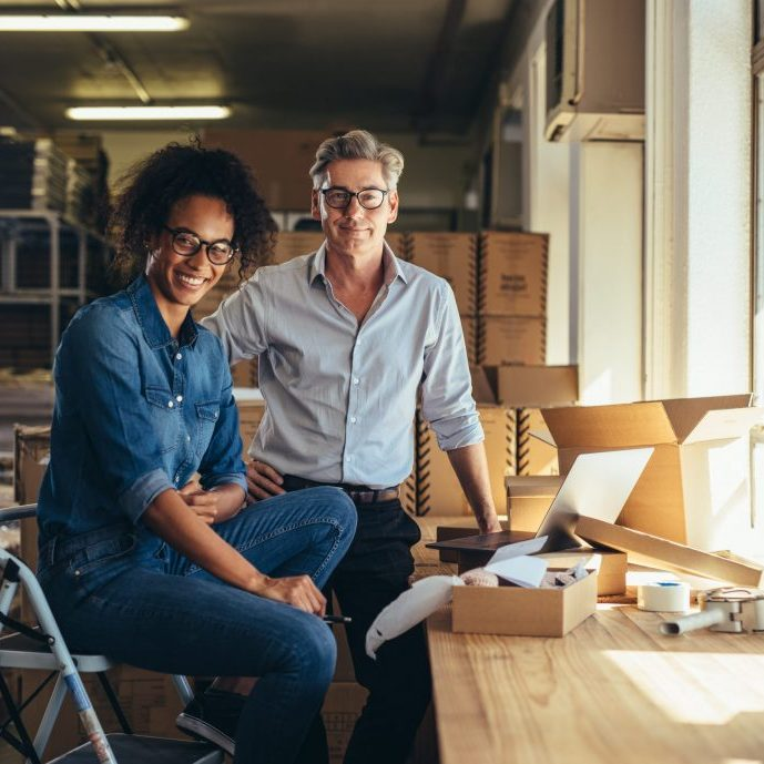 Successful online shop business partners in a small office. Male and female entrepreneurs at their online shop warehouse looking at camera and smiling.